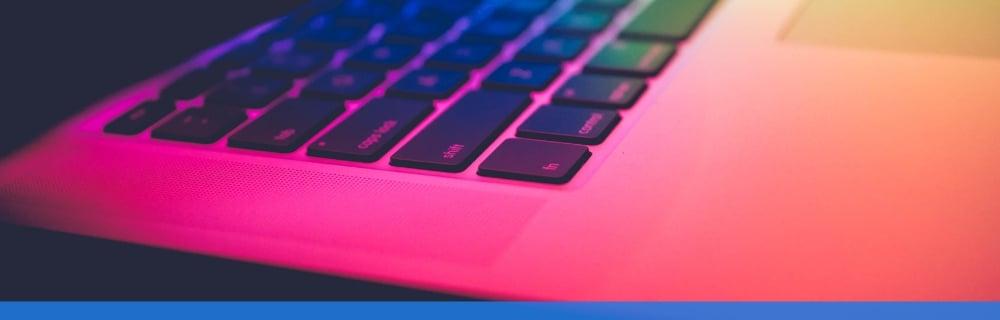 Close up of a laptop under a rainbow light