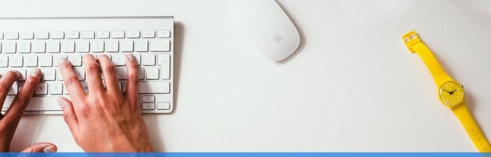 Close up of man using an apple mac white keyboard