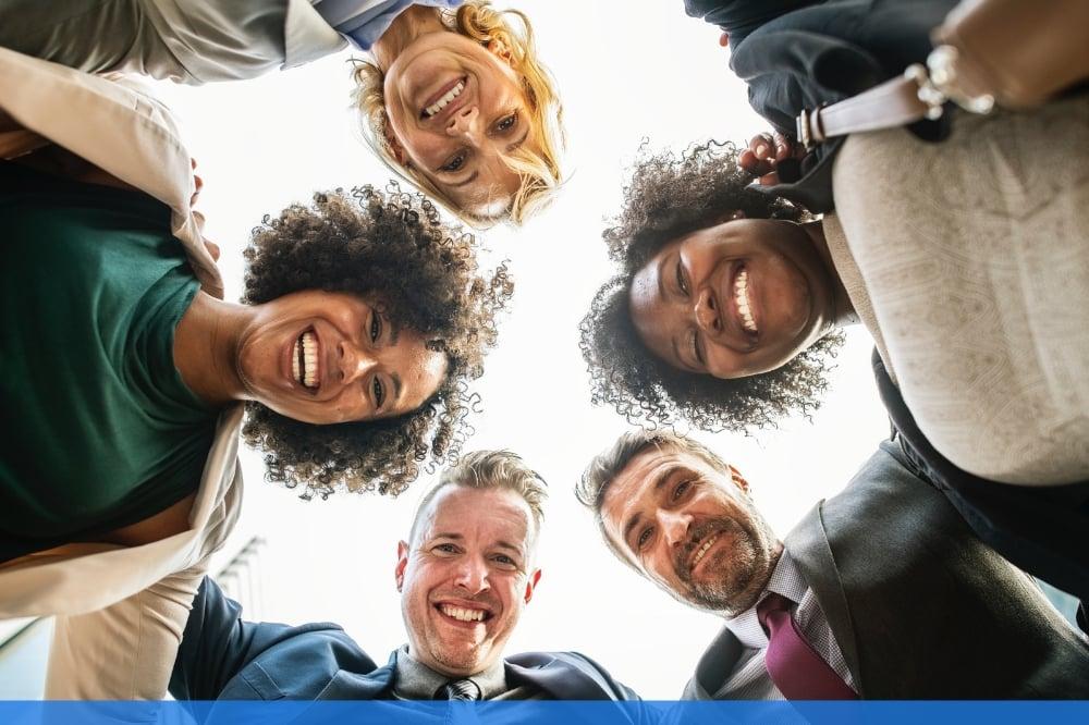 Group of employees huddled together smiling