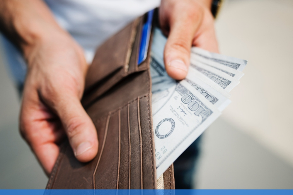 Man opening his wallet and holding 100 dollar bills