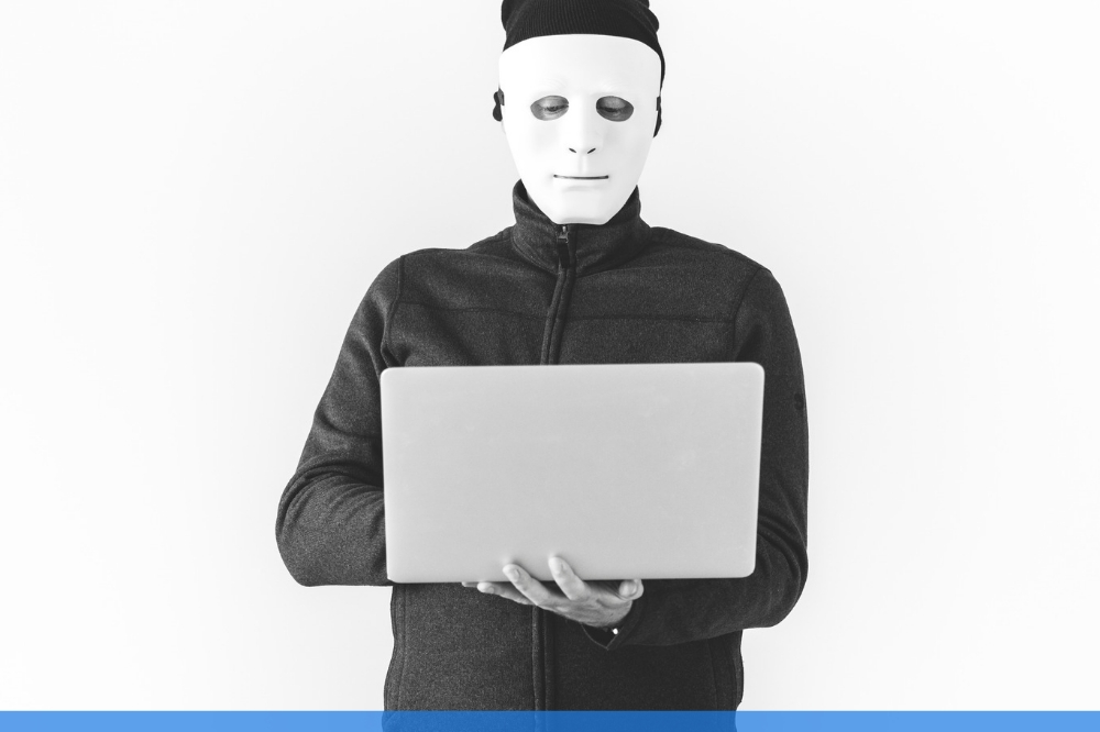 black and white image of a masked man using a laptop