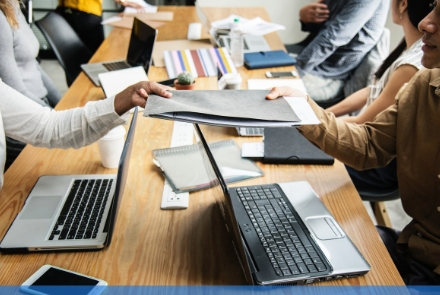 employee meeting with notes and devices on the table