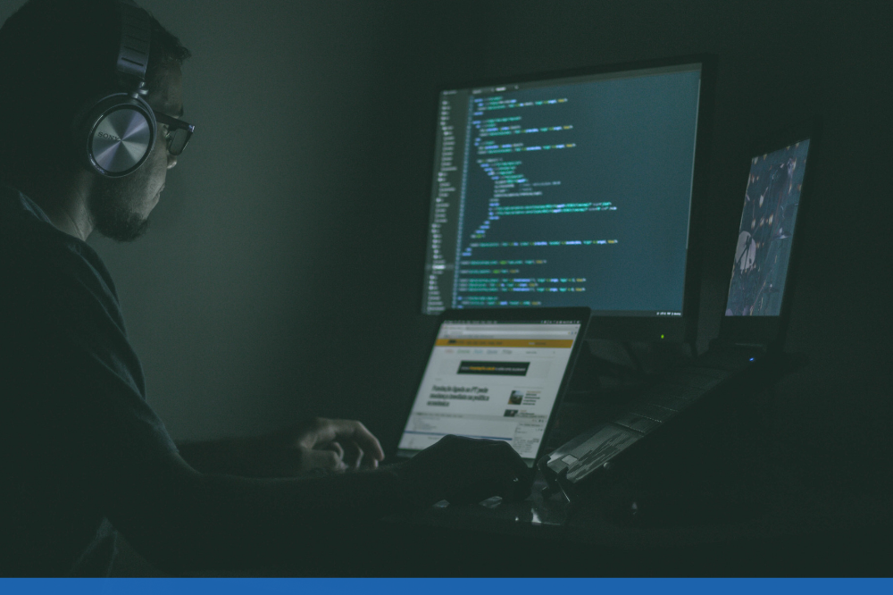 man coding at his desk