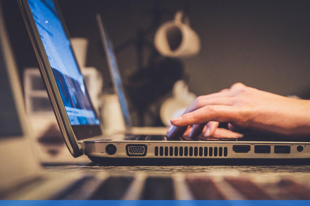 man typing on open laptop